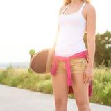 Adolescente con el monopatín, imagen con el sunflare Fotografía de archivo libre de regalías