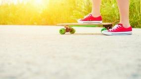 Adolescente con el monopatín, imagen con el sunflare Imagen de archivo