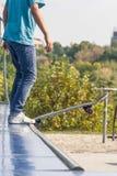 Adolescente con el monopatín listo para un truco en una media rampa del tubo Fotografía de archivo
