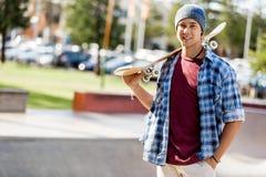 Adolescente con el monopatín que se coloca al aire libre Foto de archivo