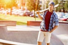 Adolescente con el monopatín que se coloca al aire libre Imágenes de archivo libres de regalías
