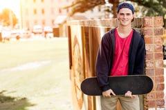 Adolescente con el monopatín que se coloca al aire libre Fotos de archivo