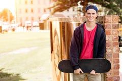 Adolescente con el monopatín que se coloca al aire libre Imagenes de archivo
