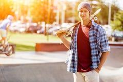 Adolescente con el monopatín que se coloca al aire libre Fotografía de archivo libre de regalías
