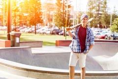 Adolescente con el monopatín que se coloca al aire libre Fotografía de archivo