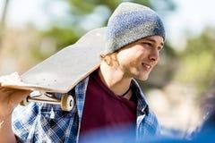 Adolescente con el monopatín que se coloca al aire libre Imagen de archivo