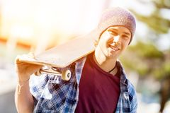 Adolescente con el monopatín que se coloca al aire libre Fotos de archivo libres de regalías