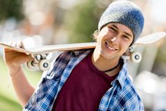 Adolescente con el monopatín que se coloca al aire libre Foto de archivo libre de regalías