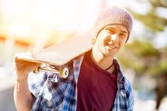 Adolescente con el monopatín que se coloca al aire libre Imagen de archivo libre de regalías