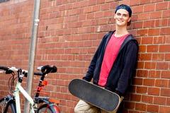 Adolescente con el monopatín que se coloca al lado de la pared Fotografía de archivo
