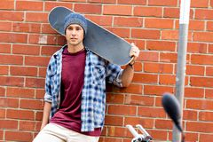 Adolescente con el monopatín que se coloca al lado de la pared Fotografía de archivo libre de regalías