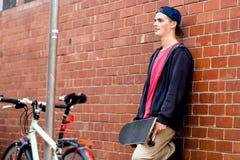 Adolescente con el monopatín que se coloca al lado de la pared Imagen de archivo