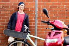 Adolescente con el monopatín que se coloca al lado de la pared Foto de archivo libre de regalías