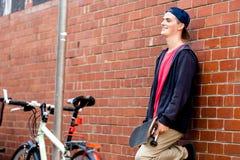 Adolescente con el monopatín que se coloca al lado de la pared Imagen de archivo libre de regalías