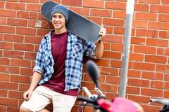 Adolescente con el monopatín que se coloca al lado de la pared Fotos de archivo libres de regalías