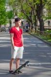 Adolescente con el monopatín que se coloca en el centro de la calle Fotografía de archivo libre de regalías