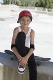 Adolescente con el monopatín que se sienta en parque del patín Imágenes de archivo libres de regalías