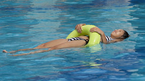 Adolescente con el neumático de la natación en el agua Imagenes de archivo