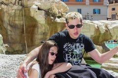 Adolescente con el novio perjudicado delante de la fuente del Trevi Fotografía de archivo libre de regalías