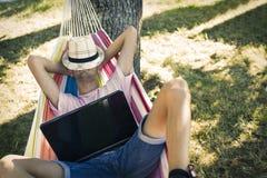 Adolescente con el ordenador portátil en la hamaca Imágenes de archivo libres de regalías