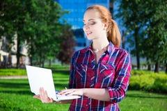 Adolescente con el ordenador portátil en parque Foto de archivo