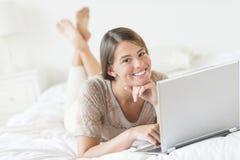 Adolescente con el ordenador portátil que miente en cama en casa Imagen de archivo libre de regalías