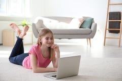 Adolescente con el ordenador portátil que miente en la alfombra acogedora Fotos de archivo libres de regalías