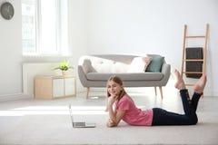 Adolescente con el ordenador portátil que miente en la alfombra acogedora Foto de archivo libre de regalías