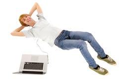Adolescente con el ordenador portátil que se acuesta Imágenes de archivo libres de regalías