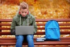 Adolescente con el ordenador portátil que se sienta en banco Imagen de archivo libre de regalías