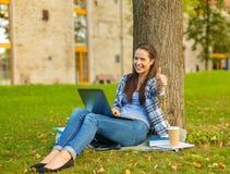 Adolescente con el ordenador portátil y el café que muestran los pulgares para arriba Imagenes de archivo