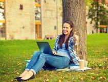 Adolescente con el ordenador portátil y el café que muestran los pulgares para arriba Imagen de archivo libre de regalías