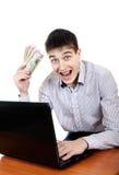 Adolescente con el ordenador portátil y el dinero Imagen de archivo