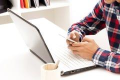 Adolescente con el ordenador portátil y el teléfono móvil Imagen de archivo libre de regalías