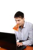 Adolescente con el ordenador portátil y la pizza Fotos de archivo