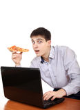 Adolescente con el ordenador portátil y la pizza Imagen de archivo libre de regalías