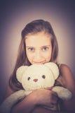 Adolescente con el oso de peluche, efecto del grano Fotografía de archivo