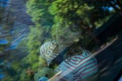 Adolescente con el oso de peluche que duerme en el asiento trasero del coche Foto de archivo libre de regalías