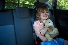 Adolescente con el oso de peluche que se sienta en el asiento trasero del coche Imagen de archivo