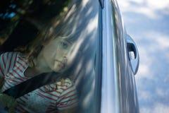 Adolescente con el oso de peluche que se sienta en el asiento trasero del coche Foto de archivo