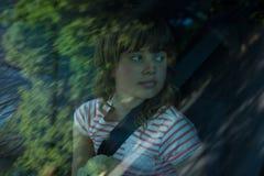 Adolescente con el oso de peluche que se sienta en el asiento trasero del coche Fotografía de archivo
