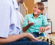 Adolescente con el papá que tiene juego de ajedrez Imágenes de archivo libres de regalías