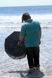 Adolescente con el paraguas que hace frente al océano Foto de archivo libre de regalías