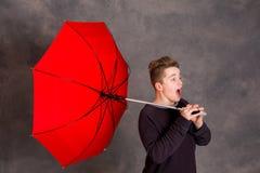 Adolescente con el paraguas rojo que se coloca en brisa fuerte Fotos de archivo