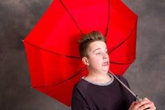 Adolescente con el paraguas rojo que se coloca en brisa fuerte Imagen de archivo