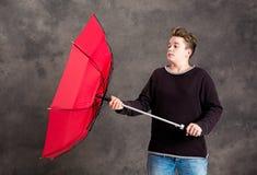 Adolescente con el paraguas rojo que se coloca en brisa fuerte Imagen de archivo libre de regalías