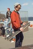 Adolescente con el patín en parque del monopatín con los amigos detrás Fotos de archivo libres de regalías