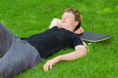 Adolescente con el patín que descansa sobre hierba Foto de archivo