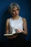 Adolescente con el pelo de plata que hojea a través del libro Cierre para arriba Fondo para una tarjeta de la invitación o una en Imagen de archivo libre de regalías