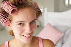 Adolescente con el pelo en bigudíes rosados Imagen de archivo libre de regalías